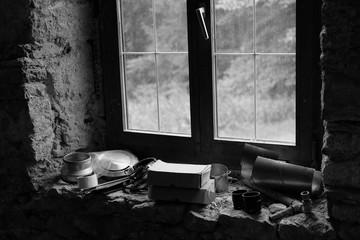 Utensilien auf der Fensterbank eines alten Bauernhaus auf dem Lande in Schwarzweiß