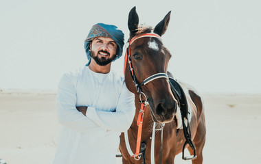Arabian man with traditional clothes riding his horse Wall mural
