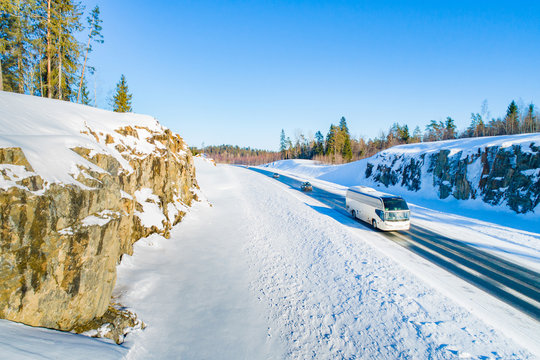 Winter journey. Bus transportation on the winter road. Road safety. Bus on the road. Snow-covered rocks and pines across the road. Trip to Karelia. Stay in the fresh air.