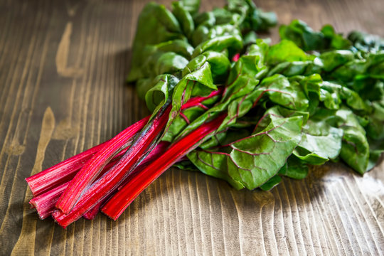 Mangold or red swiss chard leaves on wooden board