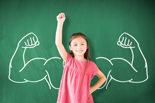 little girl standing against chalkboard and strong winner concept