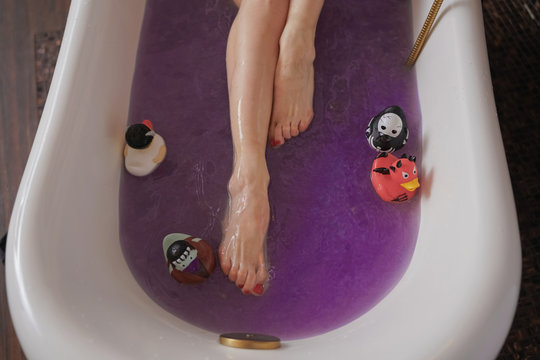 healthy naked goth girl with black hair in the luxury brown bathroom with purple salt water