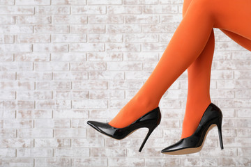 Stylish young woman in high-heeled shoes and tights on brick background Wall mural