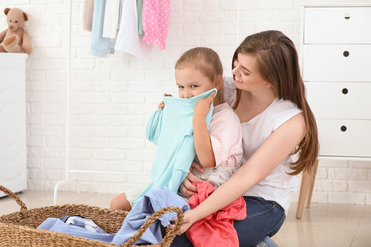Woman and her little daughter feeling smell of clean laundry at home