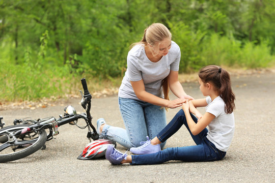Mother helping her little daughter after falling off bicycle outdoors