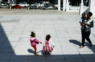 Children play as they arrive to attend a church service at the Cathedral of the Immaculate Conception, a Roman Catholic cathedral in downtown Maputo