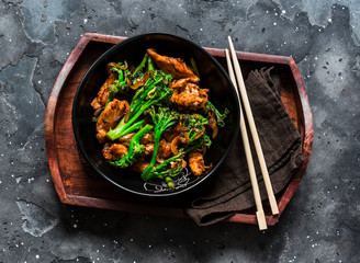 Teriyaki stir fry chicken with broccoli on wooden tray on dark background, top view