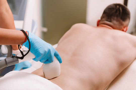 Unrecognizable man getting laser hair removal on his lower back, copy space. Beautician removing lower back hair of a male client, using laser