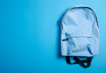 School blue backpack on blue background, top view