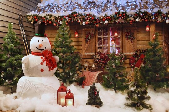 New Year's photo zone with a snowman at the house. Decor: toys, Christmas trees, skis, garland, snow, glowing light bulbs. festive mood. picture for postcard