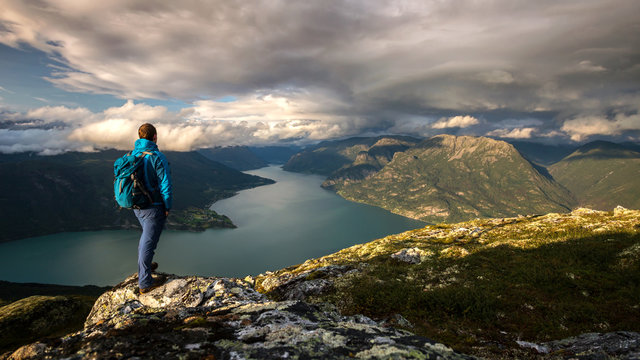 Hiker on top of mountain Molden enjoying the view of Lustrafjord, Norway
