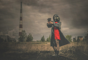 Woman in red dress and in gas mask with a toy bear is standing among burnt field on a smoking chimney background. Air pollution concept. Wall mural