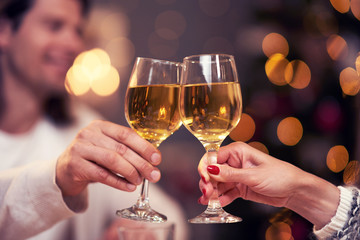 Adult couple toasting wine over Christmas background
