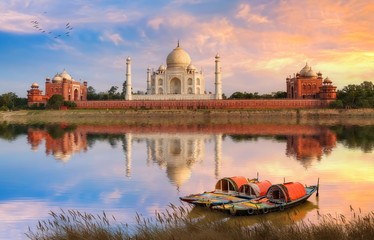 Wall Mural - Taj Mahal Agra on the banks of river Yamuna at sunset with moody sky and view of wooden boats used for tourist ride on the river