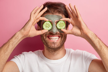 Beauty portrait of cheerful man poses with clay mask on face, two slices of cucumber on eyes, wears white t shirt, has toothy smile and bristle, poses against pink background. Cosmetology, face care