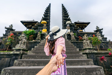 Wall Mural - Women tourists holding man's hand and leading him to Besakih temple in Bali, Indonesia.