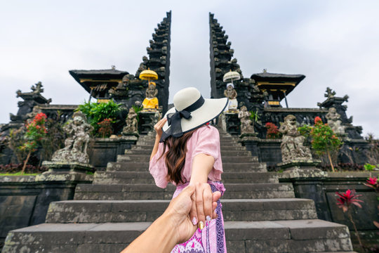 Women tourists holding man's hand and leading him to Besakih temple in Bali, Indonesia.