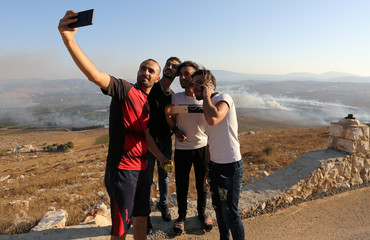 People take selfies as smoke rises from shells fired from Israel in Maroun Al-Ras village, near the border with Israel