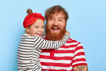 Family portrait of happy daughter wears red headband and striped jumper, embraces delighted father with thick ginger beard and curly hair, love each other very much, isolated over blue studio wall