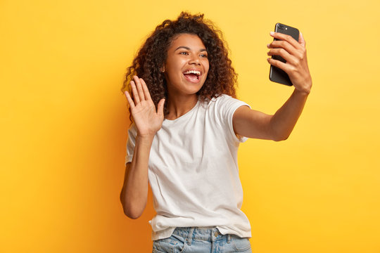 Glad dark skinned happy woman with Afro hairstyle, holds modern mobile phone in front of face, waves palm in camera, makes video call, dressed in casual wear, isolated over yellow studio wall.