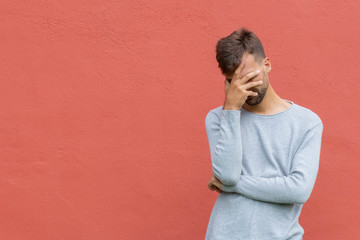 Stressed disappointed young guy making facepalm gesture with hand. Red wall background, copy space. Facepalm concept.