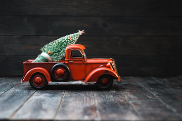 Red Toy Truck with a Christmas tree on a dark wood background