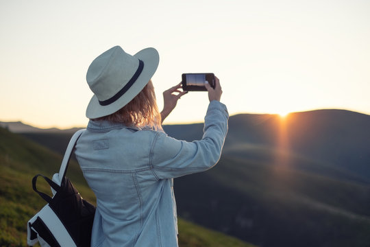 Young girl with a phone camera in the mountains during sunset. Girl and phone. Photographing landscapes by phone. Travel - Image