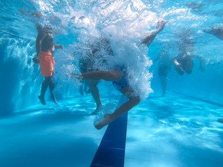 Underwater view from kids dive into a pool in a summer day