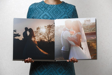 a woman holds open family photobook the person looks at the photo book sample  beige photo album  wedding photoalbum with  fabric cover.female hands holding square open photo album. Wall mural