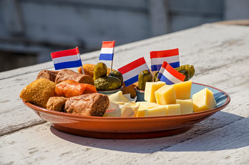 A bittergarnituur, traditional Dutch plate of pre-dinner snacks, including cheese, meatballs and pickles, decorated with flags, on a wooden table in a sunny outdoor cafe