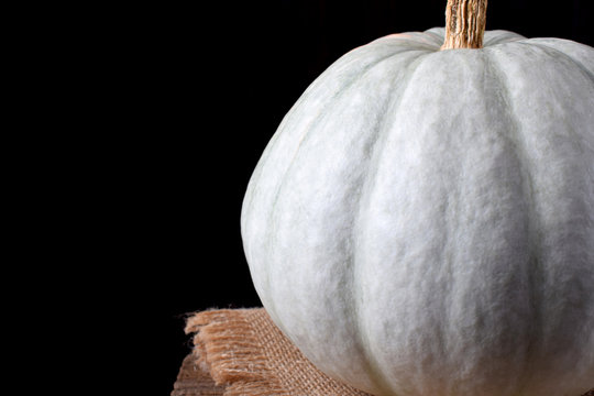 White pumpkin on the edge of the wooden table against black background