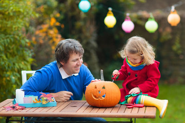 Family carving Halloween pumpkin. Wall mural