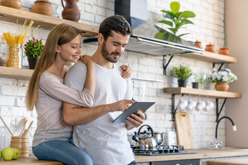 Beautiful young couple using a digital tablet and smiling while cooking in kitchen at home