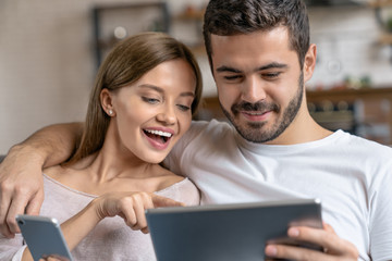 Close up shot of young happy couple hugging and using smartphone, digital tablet while sitting on sofa at home Wall mural