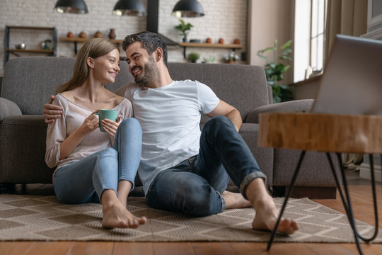 Young happy couple sitting on the floor at home and looking on each other while watching movie on laptop