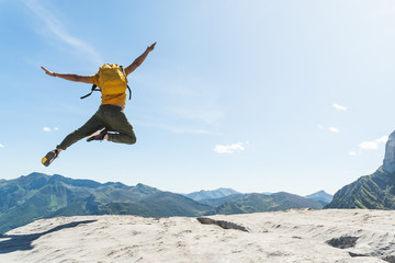 Young Man Jumping on Top of a Mountain Wearing Yellow Backpack.