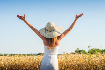 Young beautiful woman in a white dress and a hat raises her hands up on the field Wall mural