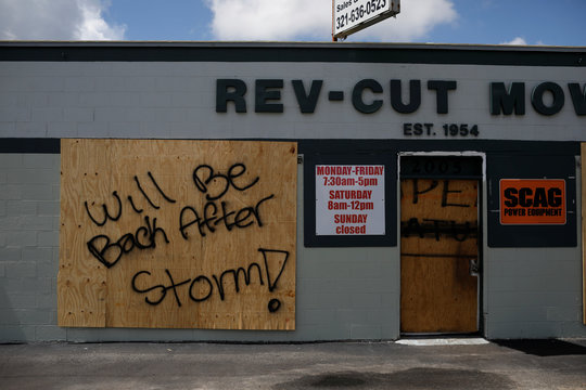 "A boarded up business with ""Will be back after storm"" painted on it is seen ahead of the arrival of Hurricane Dorian in Cocoa"