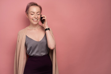A girl with short pink hair in a top and cardigan smiling speaks on the phone, closing her eyes, on a pink background.