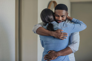 Fototapeta Affectionate young African American man hugging his wife at home obraz
