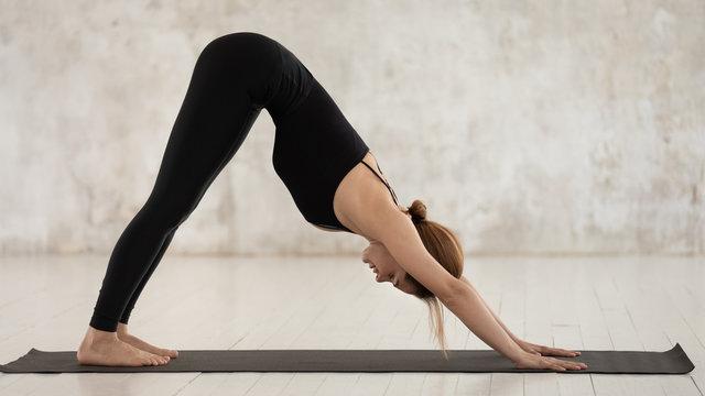 Young woman practicing yoga, Downward facing dog, adho mukha svanasana