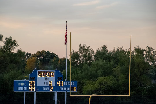Football end zone with goal posts, Amercian flag and score board during evening sunset at local high school