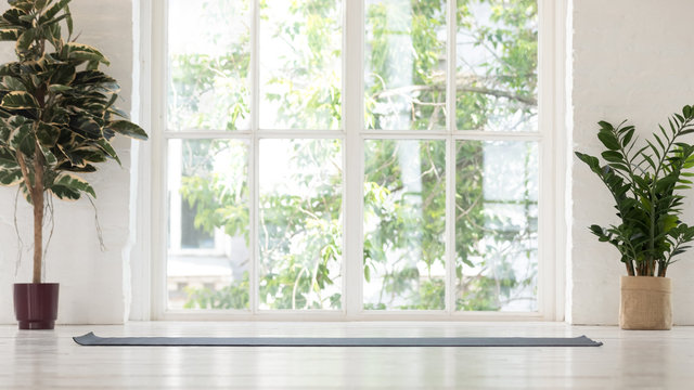 Empty yoga studio interior with windows and unrolled mat