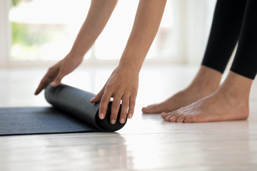 Woman practicing yoga, rolling black mat side view close up