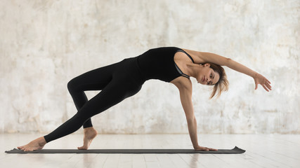 Young woman practicing yoga, standing in standing in Camatkarasana pose