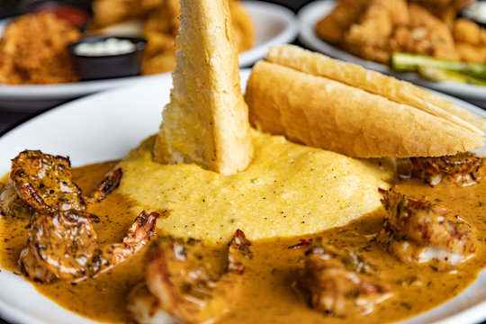 Crispy bread stuck in the grits and shrimp creole cuisine on a white plate. Close up with other platters blurred in the background