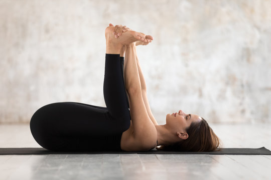 Beautiful woman practicing yoga, Happy Baby pose, Ananda Balasana