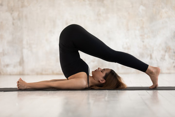 Young woman practicing yoga, Halasana exercise, Plough pose Wall mural