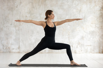 Young woman practicing yoga, standing in Warrior Two, Virabhadrasana