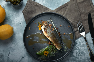 Grilled seabass with eggplant and lime. Horizontal top view, top shot. Copy space, gray concrete marble background, soft light. Food Fashion Photo.